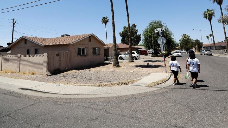 In this July 27, 2016 photo, neighborhood patrol officers Maribel Diaz Lopez, right, and Mario Ocampo walk in Phoenix past the home where a suspected serial killer murdered a man earlier in the year. The ladies were handing out an artist rendering of a the suspected serial killer and block watch flyers. The serial killer has killed seven people since March and wounded two, sowing terror in a blue-collar swath of Phoenix. Police are pleading for tips to help them catch their suspect, but many residents never report crime because they are immigrants fearing deportation. (AP Photo/Matt York)