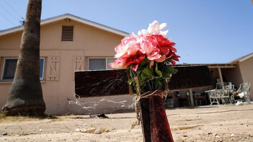 In this July 27, 2016 photo, flowers are seen outside the home where a suspected serial killer murdered a man earlier in the year in Phoenix. The serial killer has killed seven people since March and wounded two, sowing terror in a blue-collar swath of Phoenix. Police are pleading for tips to help them catch their suspect, but many residents never report crime because they are immigrants fearing deportation. (AP Photo/Matt York)