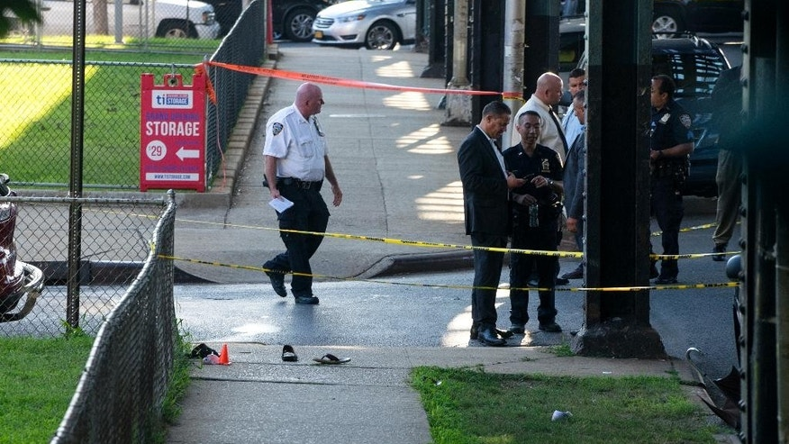 Sandals mark the crime scene, Saturday, Aug. 13, 2016, not far from the Al-Furqan Jame Masjid Mosque in the Ozone Park neighborhood of Queens, New York, where the leader of a New York City mosque has been fatally shot and an associate has been wounded in a brazen daylight attack. (AP Photo/Craig Ruttle)