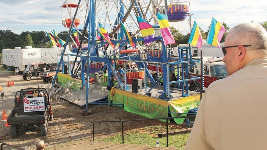 Law enforcement cordon off the area surrounding the Ferris wheel Monday, Aug. 8, 2016, after three people fell from the ride during a county fair in Greenville, Tenn. Baileyton police Officer Kenneth Bitner is visible at right. Police say one of three people who fell from the Ferris wheel suffered a head injury and remains hospitalized in serious condition. (O.J. Early/The Greeneville Sun via AP)