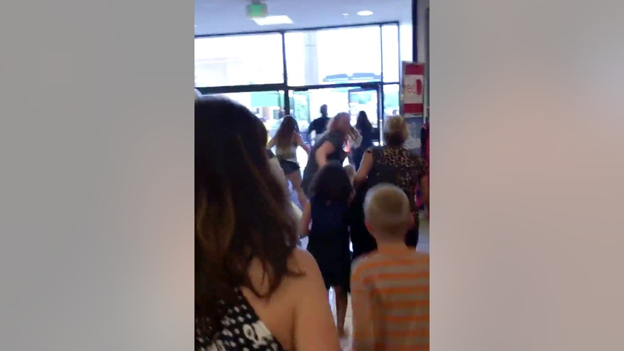 In this image made from a video provided by Lauren Baker, people rush to one of the exits of Crabtree Valley Mall in Raleigh, N.C. Saturday, Aug. 13, 2016. Reports of gunshots inside the busy North Carolina mall caused chaos Saturday afternoon as shoppers ran screaming for the doors or sheltered in stores while dozens of officers arrived on the scene, witnesses said. (Lauren Baker via AP)