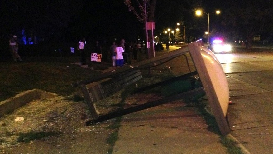 An overturned bus shelter lies on the ground after dozens of people protested following the fatal shooting of a man in Milwaukee, Saturday, Aug. 13, 2016. A crowd of protesters skirmished with police Saturday night in the Milwaukee neighborhood where an officer shot and killed a man after a traffic stop and foot chase earlier in the day, setting fire to a police car and torching a gas station. (AP Photo/Gretchen Ehlke)