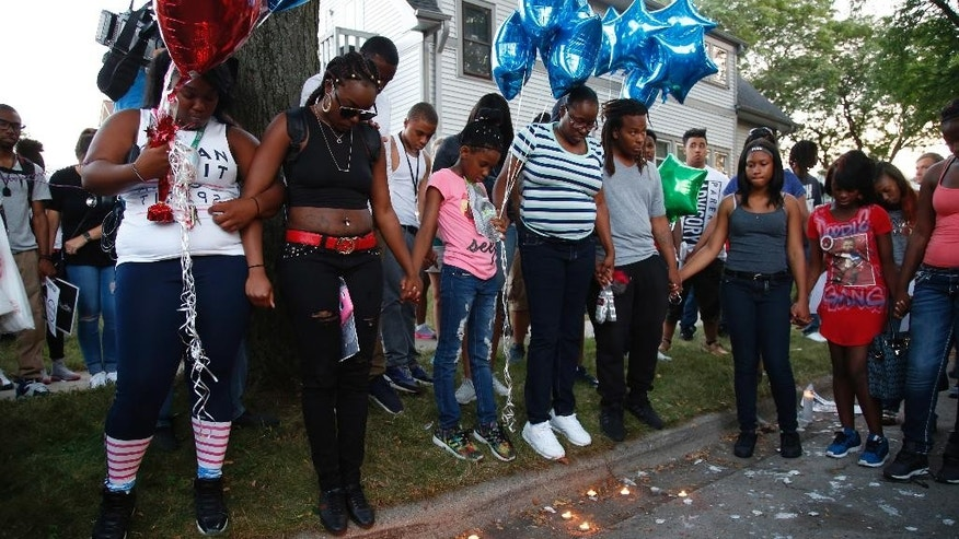 Family members of Sylville Smith gather where he was shot and killed by Milwaukee Police in Milwaukee, Sunday, Aug. 14, 2016. The black man whose killing by police touched off rioting in Milwaukee was shot by a black officer after turning toward him with a gun in his hand, the police chief said Sunday, as Wisconsin's governor put the National Guard on standby against any further violence on the city's mostly black north side. (AP Photo/Jeffrey Phelps)