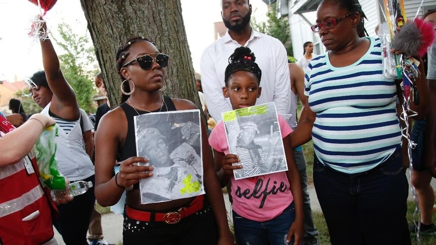 Family members of Sylville Smith gather where he was shot and killed by Milwaukee police in Milwaukee, Sunday, Aug. 14, 2016. Police in Milwaukee say a black man whose killing by police touched off arson and rock-throwing was shot by a black officer after turning toward him with a gun in his hand. Wisconsin's governor, meanwhile, has put the National Guard on standby in case of more violence Sunday night. (AP Photo/Jeffrey Phelps)
