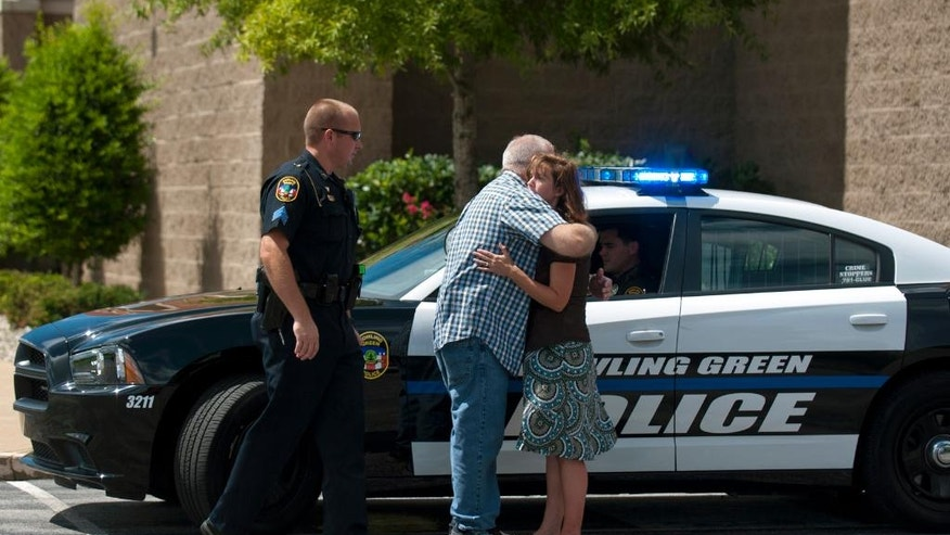 A man embraces a woman as she arrives on scene to talk to Bowling Green Police, Sunday, Aug. 14, 2016, after a man allegedly stabbed his father during a church service at Hillvue Heights Baptist Church in Bowling Green, Ky. The victim was taken to a hospital where his condition wasn't immediately known. (Miranda Pederson/Daily News via AP)