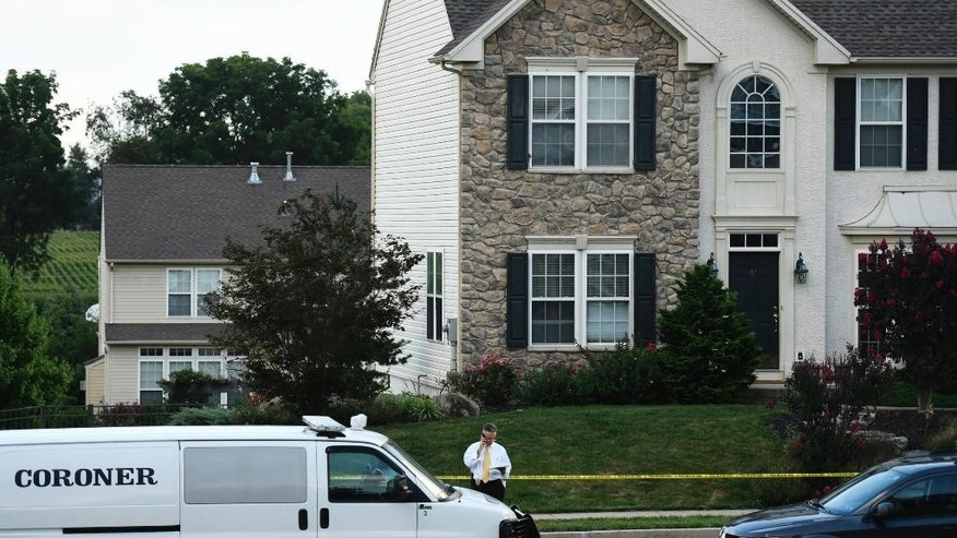 FILE - In this Aug. 6, 2016, file photo, Berks County Detective Michael J. Gombar investigates outside a house where Megan Short was found dead alongside her husband Mark Short Sr. and the couple's three children Liana, Mark Jr. and Willow in Sinking Spring, Pa. Berks County District Attorney John Adams said Monday, Aug. 15, 2016, that Mark Short Sr. bought a gun a day after police responded to a domestic dispute call on July 18, 2016, before killing his wife Megan and the couple's three children on Aug. 6, 2016. The family had been featured in news stories about difficulties getting medication for their daughter Willow, who received a heart transplant when she was 6 days old. (Jeremy Drey/Reading Eagle via AP, File)