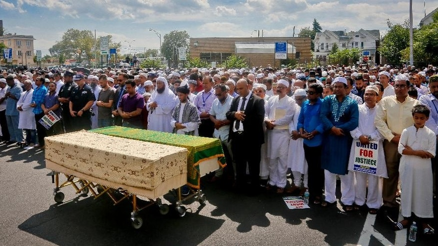 Thousands gather to pray at caskets of Imam Maulama Akonjee, draped in green top, and Thara Uddin in a municipal parking lot, Monday Aug. 15, 2016, in New York. Both were shot in the head as they left the Al-Furqan Jame Masjid mosque in the Ozone Park section of Queens as they left afternoon prayers Saturday. (AP Photo/Bebeto Matthews)