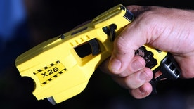 A municipal policeman in Nice poses with the Taser X26 model during a presentation in Nice, south eastern France May 27, 2010.  REUTERS/Sebastien Nogier (FRANCE - Tags: CRIME LAW) - RTR2EFNY