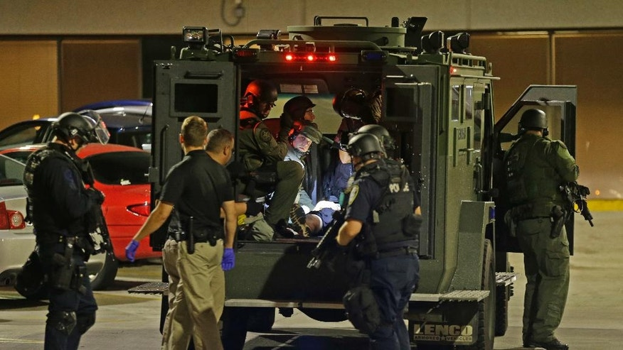 Armed police officers transport an injured man in an armored vehicle to a hospital Milwaukee, Sunday, Aug. 14, 2016. Shots rang out during unrest after a police shooting that killed a man Saturday. Police said one person was shot at a Milwaukee protest on Sunday and officers used an armored vehicle to retrieve the injured victim and take the person to a hospital, as tense skirmishes erupted for a second night following the police shooting of a black man. (AP Photo/Jeffrey Phelps)