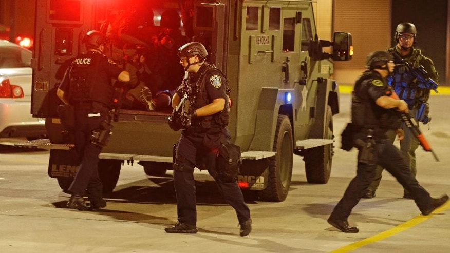 Police transport a man who was apparently shot during unrest in Milwaukee to a hospital, Sunday, Aug. 14, 2016. Shots rang out during unrest after a police shooting that killed a man Saturday. Police said one person was shot at a Milwaukee protest on Sunday and officers used an armored vehicle to retrieve the injured victim and take the person to a hospital, as tense skirmishes erupted for a second night following the police shooting of a black man. (AP Photo/Jeffrey Phelps)