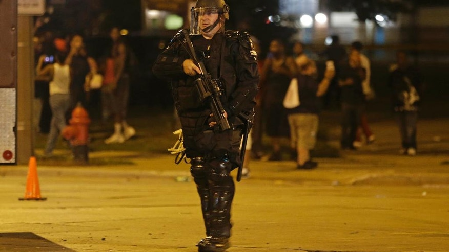 Police move in on people throwing rocks at police in Milwaukee, Sunday, Aug. 14, 2016. Shots rang out during unrest after a police shooting that killed a man Saturday. Police said one person was shot at a Milwaukee protest on Sunday and officers used an armored vehicle to retrieve the injured victim and take the person to a hospital, as tense skirmishes erupted for a second night following the police shooting of a black man. (AP Photo/Jeffrey Phelps)