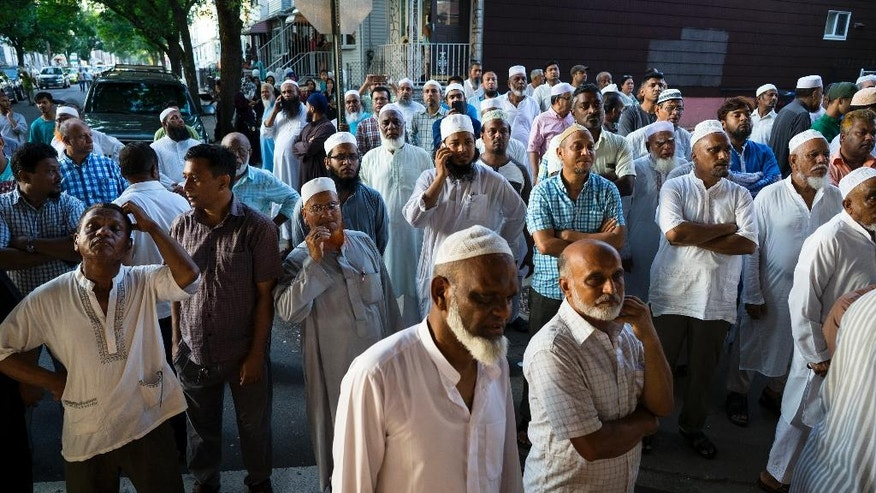 In this Saturday, Aug. 13, 2016, photo, people gather near a crime scene for a demonstration after the leader of a New York City mosque and an associate were fatally shot in a brazen daylight attack as they left afternoon prayers Saturday. Police said 55-year-old Imam Maulama Akonjee and his 64-year-old associate, Tharam Uddin, were shot in the back of the head as they left the Al-Furqan Jame Masjid mosque in the Ozone Park section of Queens shortly before 2 p.m. (AP Photo/Craig Ruttle)