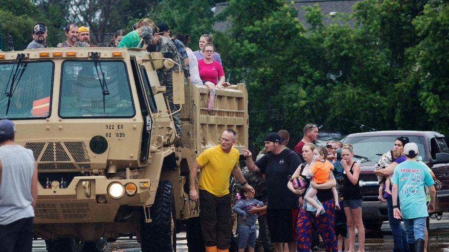 Members of the Louisiana Army National Guard unload people at a rally point after they were rescued from rising floodwater near Walker, La., after heavy rains inundated the region, Sunday, Aug. 14, 2016. (AP Photo/Max Becherer)