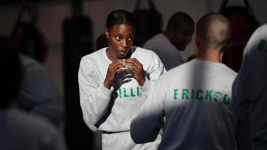 In this Friday, July 29, 2016 photo, Los Angeles County sheriff's deputy recruit Renata Phillip, center, trains with Steve Erickson during a defensive tactics class at the Biscailuz Regional Training Center in Monterey Park, Calif. Phillip is one of just two black women in her class of 84 recruits. More than half are men and most are white or Hispanic. Only three recruits out of every 100 will make it to graduation, said Capt. Scott Gage, who's in charge of training at the Los Angeles County Sheriff's Department.  (AP Photo/Jae C. Hong)