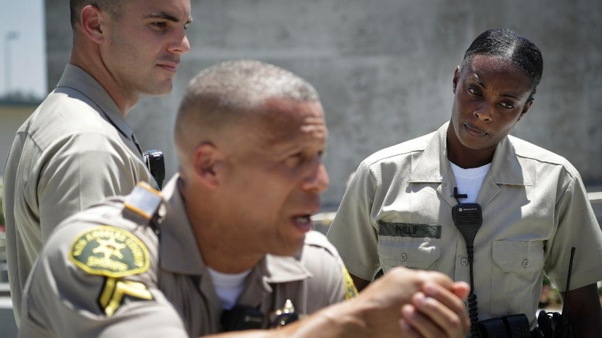 """In this Tuesday, July 19, 2016 photo, Los Angeles County sheriff's deputy recruit Renata Phillip, right, listens to recruit training officer Sean Essex at the Biscailuz Regional Training Center in Monterey Park, Calif. Phillip hopes to be an example to those who've never dealt with a black law enforcement officer. """"If I can have a positive experience with someone and maybe help them change their mind, why not?"""" she said. (AP Photo/Jae C. Hong)"""
