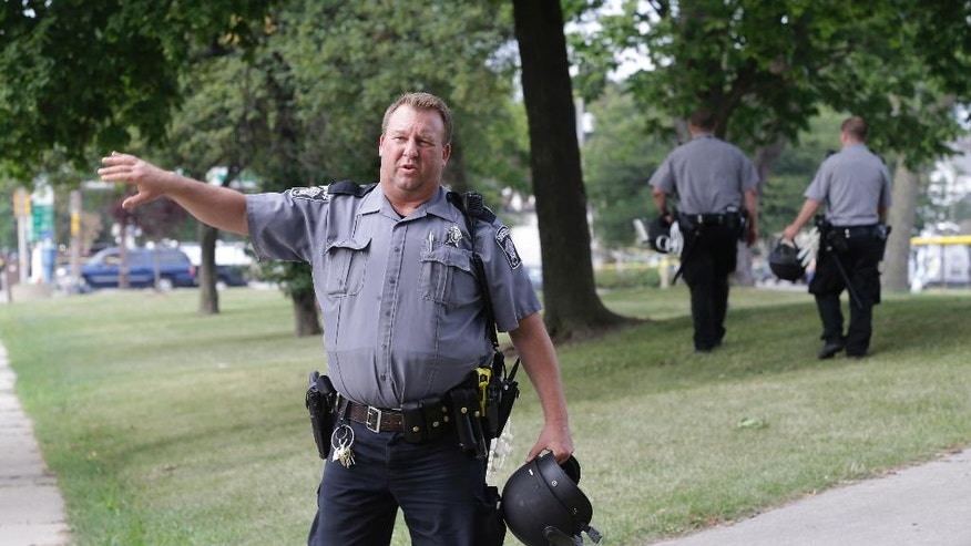 "Police prepare to close a park in Milwaukee, Monday, Aug. 15, 2016. Following a night of violence that left half a dozen businesses in flames, the Milwaukee police chief expressed surprise at the level of unrest that erupted after the fatal shooting of a black man by a black officer. ""This was, quite frankly, unanticipated,"" Chief Edward Flynn said Monday, two days after the worst of the rioting hit the Sherman Park neighborhood on the city's economically depressed and largely black north side. (AP Photo/Jeffrey Phelps)"