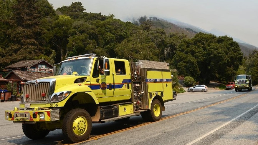 A fire engine passes the Ripplewood Resort as a smoke from a firing operation is visible in the Juan Higuera Creek drainage above as crews fight a wildfire near the village of Big Sur, Calif., Saturday, Aug. 13, 2016. (David Royal/The Monterey County Herald via AP)