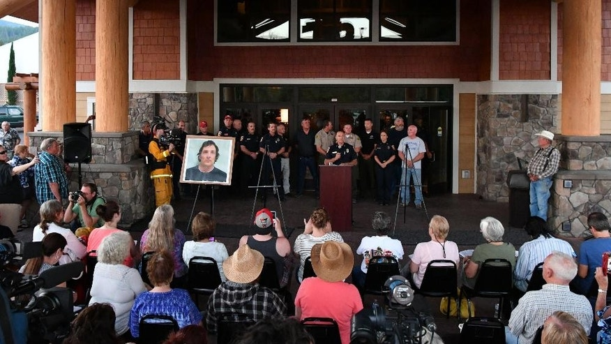 People look on as its announced that Damin Pashilk, seen here in a poster on display at Twin Pines Casino, is the arsonist allegedly responsible for a wildfire that exploded over the weekend in a Northern California town, in Middletown, Calif. on Monday, Aug. 15, 2016. Pashilk is being charged with 17 counts of arson and is in jail. (AP Photo/Josh Edelson)
