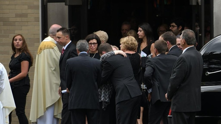 Mourners console each other outside Our Lady of the Lake Roman Catholic church  after her funeral service for Vanessa Marcotte, Tuesday, Aug. 16, 2016, in Leominster, Mass. Marcotte, 27, who worked for Google in New York City, was killed Aug. 7, while out running near her mother's Massachusetts home. Investigators have received more than 600 tips, but no arrests have been announced. They say her male assailant may have suffered cuts, scratches and bruises from a struggle. (Christine Peterson/Worcester Telegram & Gazette via AP)