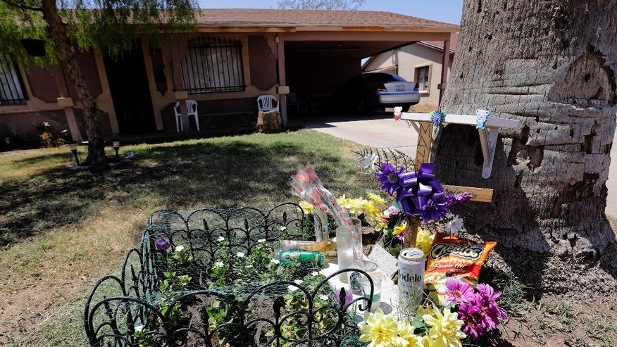 FILE--In this July 27, 2016, file photo, a makeshift memorial is seen outside the home where a suspected serial killer murdered a man earlier in the year in Phoenix. Authorities have released police reports on two of seven shooting deaths that investigators believed were carried out by a serial killer. The reports detail the shooting deaths of Manual Castro Garcia and Horacio de Jesus Pena, who died a week apart in June in the city's Maryvale neighborhood. (AP Photo/Matt York, file)