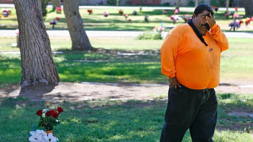 """FILE--In this July 14, 2016, file photo, Margarito Castro, father of Manuel """"Manny"""" Castro Garcia, 19, pauses for a moment as he visits his son's grave at a cemetery in Phoenix, Ariz. Authorities have released police reports on two of seven shooting deaths that investigators believed were carried out by a serial killer. The reports detail the shooting deaths of Manual Castro Garcia and Horacio de Jesus Pena, who died a week apart in June in the city's Maryvale neighborhood. (AP Photo/Ross D. Franklin, file)"""