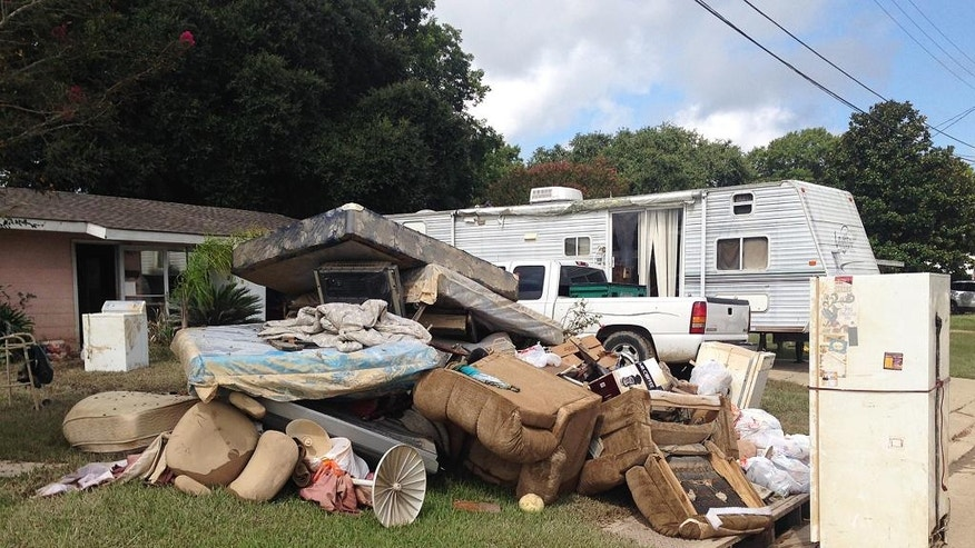 A growing pile of debris sits outside the flood-ravaged home of Carolyn and James Smith in Denham Springs, La. on Wednesday, Aug 17, 2016. Smith says she and four other adults will live for the time being in the travel trailer that one of her sons towed to the driveway after weekend flooding inundated the area. (AP Photo/Kevin McGill)