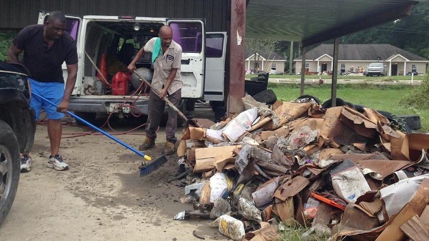 Terry Brewer, left, and Timothy Harris pile up debris outside a flooded auto parts store in Albany, La. on Wednesday, Aug 17, 2016. The U.S. Small Business Administration plans to open several south Louisiana locations to help businesses damaged by record flooding. Louisiana's economic development office is encouraging business owners to register for federal disaster aid and to look at other available support services at www.OpportunityLouisiana.com. (AP Photo/Kevin McGill)