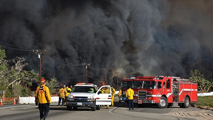This Tuesday, Aug. 16, 2016 photo Heavy fire envelopes Hwy 138 at Hess Rd in Phelan, Calif. as firefighters prepare to battle a wildfire spreading through San Bernardino County. Officials in charge of the battle against California's newest huge wildfire estimate that only about half of the 4,500 residents of the threatened town of Wrightwood have complied with evacuation orders. The fire is climbing the flanks of the San Gabriel Mountains, where Wrightwood sits at an elevation around 5,900 feet. (AP Photo/Rick McClure)2