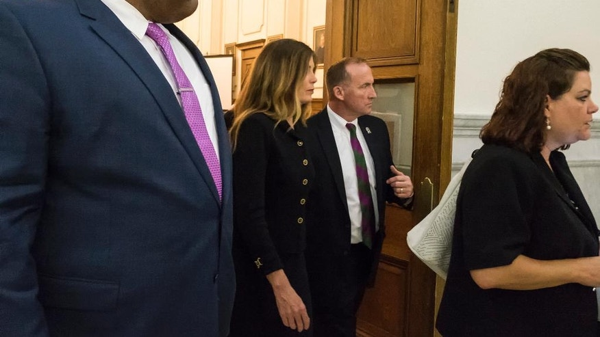 Pennsylvania Attorney General Kathleen Kane, second left, is escorted out of the Montgomery County courtroom by Bob Ruddy her prime security agent in Norristown, Pa., Monday, Aug. 15, 2016. Kane showed little emotion as the jury convicted her late Monday of all nine counts, including two felony perjury counts. (Ed Hille/The Philadelphia Inquirer via AP, Pool)