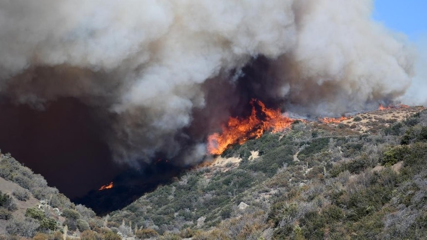 Smoke billows out as wildfire flames spread over hills, seen from Lytle Creek Road in Lytle Creek, Calif., Tuesday, Aug. 16, 2016. (David Pardo/The Daily Press via AP)