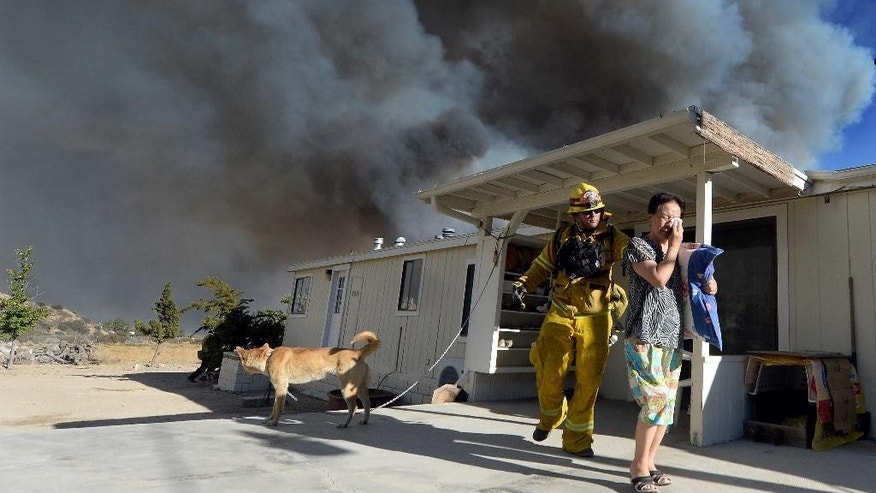 San Bernardino County Firefighter/Engineer/Paramedic Jeremy Pendergraft helps a couple evacuate out of their home as she cries off of Hess Rd. as a wildfire off of Hwy 138 quickly approaches in San Bernardino, Calif., Tuesday Aug. 16, 2016. Eric Sherwin of the San Bernardino County Fire Department says the blaze that began in the Cajon Pass continues to race in several directions. It has topped ridges in the San Bernardino Mountains and is closing in on high desert communities on the other side. (Will Lester/The Inland Valley Daily Bulletin via AP)