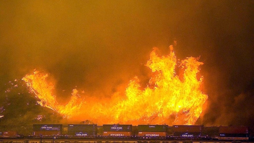 Flames erupt on a hillside alongside one of the main rail routes connecting Southern California with points north and east as a wildfire rages out of control in Cajon Pass north of Devore, Calif., Tuesday, Aug. 16, 2016. The fire was roaring through the San Bernardino Mountains, heading generally north but also east and west above the Cajon Pass, and forced the shutdown of a section of Interstate 15, the main highway between Los Angeles and Las Vegas, leaving commuters stranded for hours. The growth was explosive, San Bernardino County fire spokesman Eric Sherwin said. (Doug Saunders/The Sun via AP)