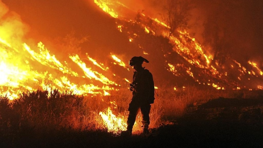 FILE - In this Aug. 3, 2015 file photo, CalFire firefighter Bo Santiago lights a backfire as the Rocky fire burns near Clearlake, Calif. The Rocky Fire that destroyed 43 homes in 2015 in a largely rural area north of San Francisco was sparked by an illegal marijuana growing operation, officials said Wednesday, Aug. 17, 2016. Two suspects fled the country before they could be questioned. (AP Photo/Josh Edelson, File)