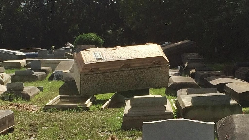 In this image made from video, Coffins lie unearthed Thursday, Aug. 18, 2016, in Plainview Cemetery in Denham Springs, La. With an estimated 40,000 homes damaged by deadly flooding, Louisiana could be looking at its biggest housing crunch since the miserable, bumbling aftermath of Hurricane Katrina a decade ago. (AP Photo/Joshua Replogle)