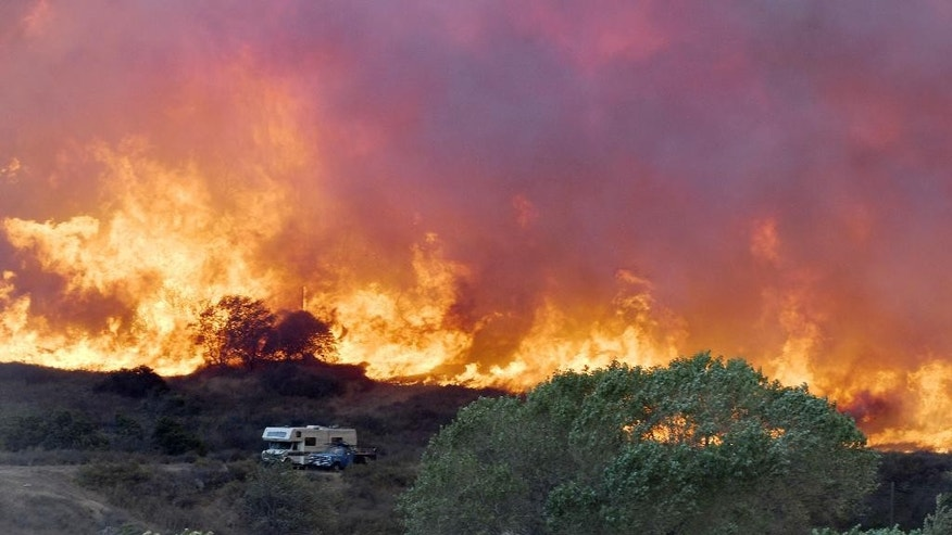 Flames from the Bluecut Fire approach an RV and a vehicle in Devore, Calif, on Wednesday, Aug. 17, 2016. (David Pardo/The Victor Valley Daily Press via AP)