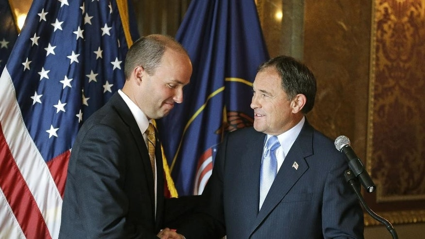 FILE - In this Oct. 8, 2013, file photo, Spencer Cox, left, shakes hands with Gov. Gary Herbert after he was announced as the state's new lieutenant governor during a news conference in Salt Lake City. Cox said he won't support Donald Trump unless the GOP nominee dramatically changes his tone, The Salt Lake Tribune published Saturday, Aug. 13, 2016. (AP Photo/Rick Bowmer, File)