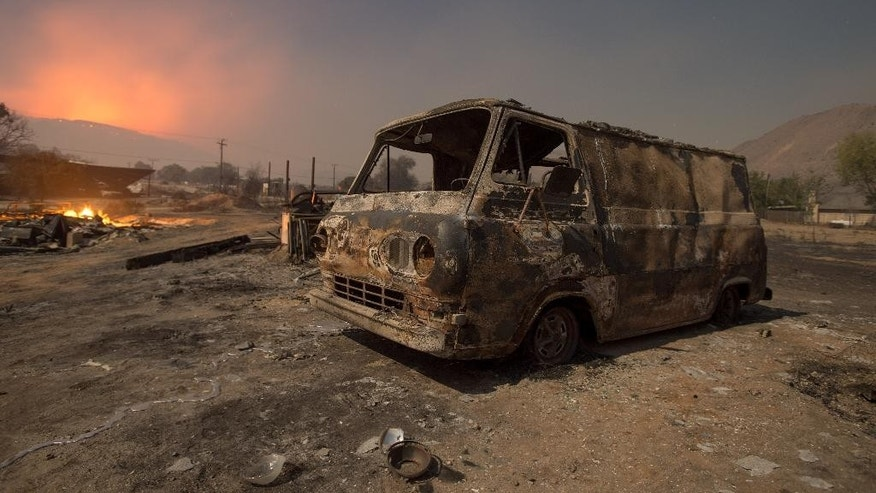 Seen in a long exposure nighttime photograph, a burned van rests in a lot while a wildfire glows on the horizon in Phelan, Calif., early Thursday, Aug. 18, 2016 2016. (AP Photo/Noah Berger)