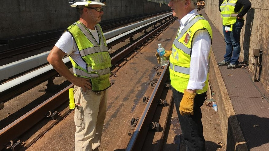 In this photo taken July 25, 2016, Metro General Manager Paul Wiedefeld, right, chats with an employee during a tour of track work being done on Metro's orange line in northern Virginia. Wiedefeld ordered the track work, which requires trains in both directions to share a single line, as part of his effort to make the deteriorating system safer and more reliable. (AP Photo/Ben Nuckols)