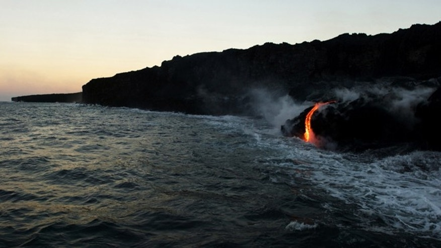 In this Tuesday, Aug. 9, 2016 photo, lava from Kilauea, an active volcano on Hawaii's Big Island, flows into the ocean as seen from a boat operated by Lava Ocean Tours off the coast of Volcanoes National Park near Kalapana, Hawaii.