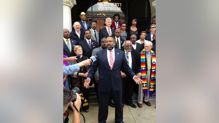 Attorney Nimrod Chapel Jr., who is president of the Missouri NAACP, speaks to reporters Thursday, Aug. 18, 2016, at the Cole County Courthouse in Jefferson City, Mo. Nimrod helped represent 22 faith leaders, some of whom are standing behind him, who were convicted of trespassing for a 2014 protest in the Missouri Senate in support of expanded Medicaid eligibility for low-income adults. (AP Photo/David Lieb)