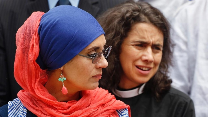 Debbie Almontaser, left, with the Muslim Community Network, and Rev. Chloe Breyer, join with members of the Islamic and interfaith community for a news conference regarding the murders of Imam Maulana Alauddin Akonjee and Thara Uddin, Thursday, Aug. 18, 2016, at City Hall in New York. The pair were gunned down Saturday after leaving a mosque in Queens. Oscar Morel has been charged in the murders. (AP Photo/Mark Lennihan)