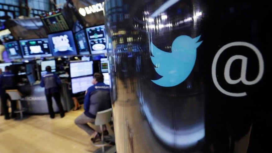 FILE - In this Tuesday, Oct. 13, 2015, file photo, the Twitter logo appears on a phone post on the floor of the New York Stock Exchange.  Twitter said Thursday, Aug. 18, 2016,  it has suspended 360,000 accounts since mid-2015 for violating its policies banning the promotion of terrorism and violent extremism.  (AP Photo/Richard Drew, File)