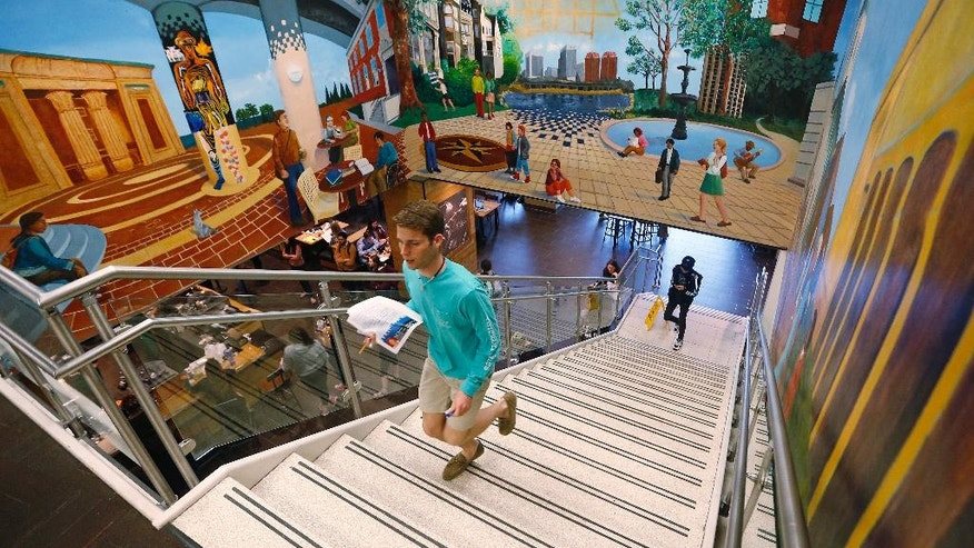 A student walks up stairs surrounded by colorful murals at the renovated James Branch Cabell Library on the campus of Virginia Commonwealth University in Richmond, Va., on April 28, 2016. The renovation opened the library to let in natural light and add more seating, group work rooms and a large coffee shop. (AP Photo/Steve Helber)