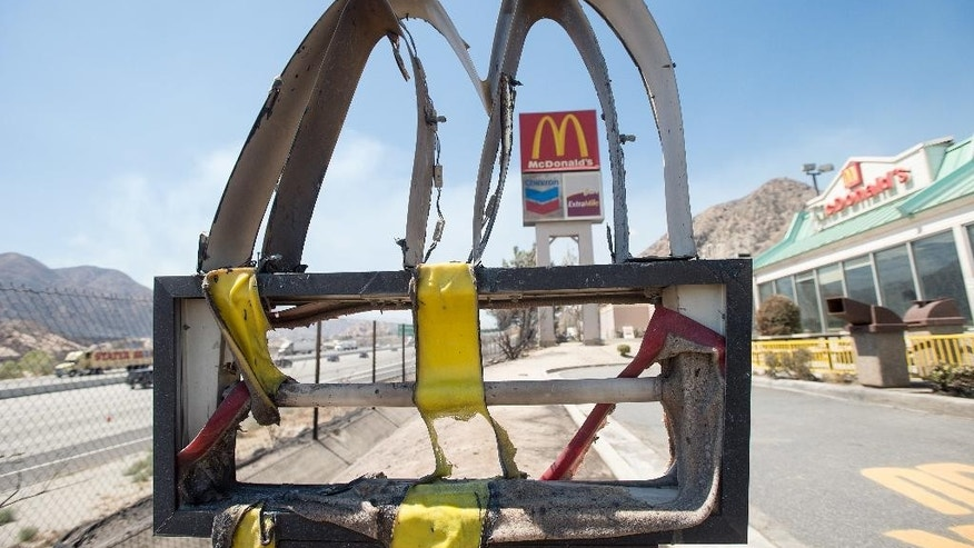 Following a wildfire, a melted McDonald's sign stands outside a restaurant in Cajon Junction, Calif., on Thursday, Aug. 18, 2016. Scenes of destruction were everywhere Thursday after a huge wildfire sped through mountains and high desert 60 miles east of Los Angeles so swiftly that it took seasoned firefighters off guard. (AP Photo/Noah Berger)