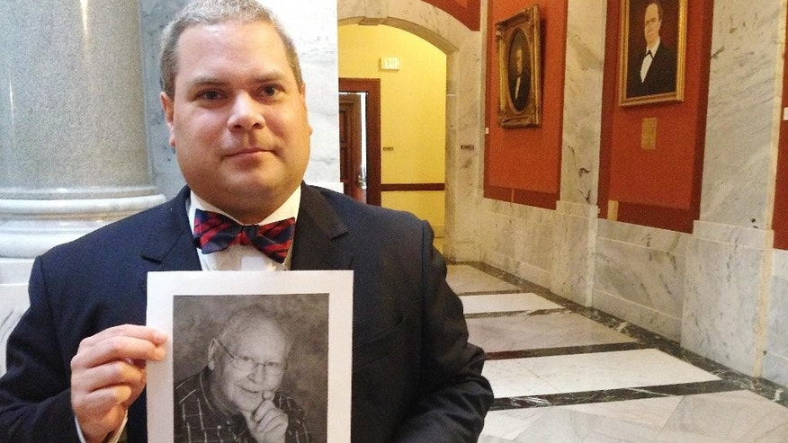 Attorney Steven Megerle holds a photo of his client, Elmer Riehle, outside of the Kentucky Supreme Court on Friday, Aug. 19, 2016, in Lexington, Ky. A jury declared Riehle mentally incompetent in 2008 and appointed his wife as his legal guardian. Now, Riehle wants a divorce. But Kentucky law won't allow it. The state Supreme Court will decide. (AP Photo/Adam Beam)