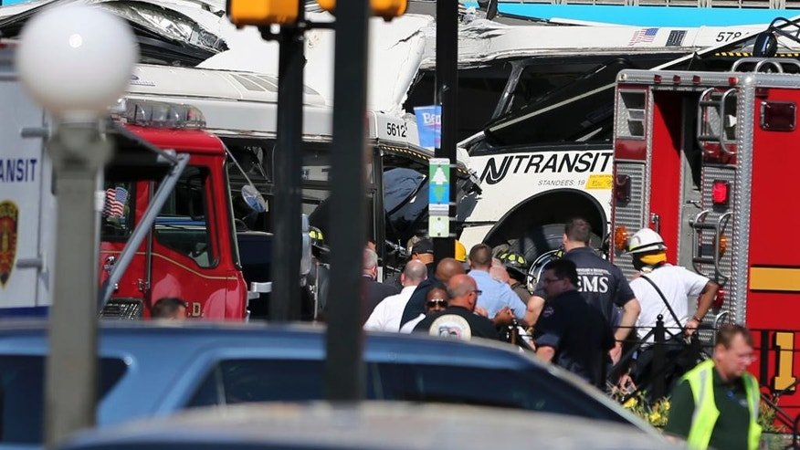 Police, firefighters and EMS personnel work at the scene on Broad Street after two commuter buses collided in Newark, N.J., Friday, Aug. 19, 2016.  Investigators are trying to determine if a commuter bus ran a red light and broadsided another commuter bus, killing a driver and injuring several.   (AP Photo/Mel Evans)