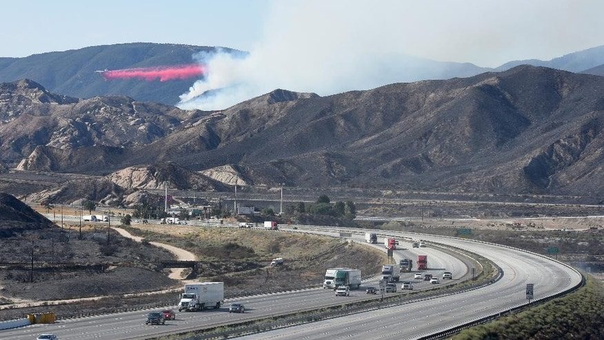 A DC-10 drops fire retardant on a wildfire as southbound Interstate 15 remains closed in the Cajon Pass, Calif., on Thursday, Aug. 18, 2016.  The California Highway Patrol reopened I-15 late Wednesday night, while the southbound side remained closed. Reopening the south side Thursday depended on repair of guardrails. (David Pardo/The Daily Press via AP)