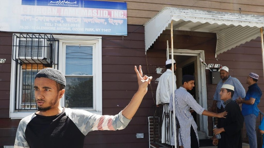 In this Wednesday, Aug. 17, 2016, photo Ashik Uddin gestures as he speaks during an interview with The Associated Press outside the Al-Furqan Jame mosque in the Ozone Park neighborhood of the Queens borough of New York.  The shooting of an imam and his assistant near their New York mosque has unnerved Muslim residents of the Ozone Park section of Queens.  (AP Photo/Mary Altaffer)