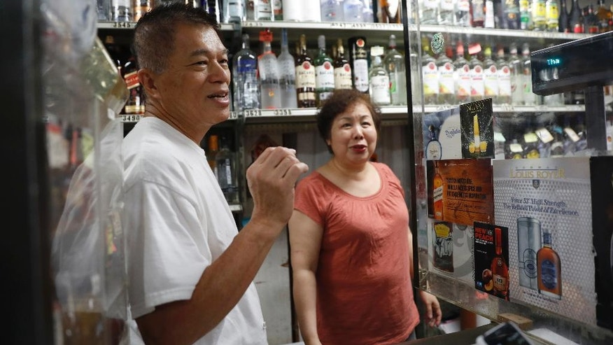 In this Wednesday, Aug. 17, 2016, photo Johnny, left, and Sally Lee speak during an interview with The Associated Press at their Liquor store in the Ozone Park neighborhood of the Queens borough of New York. (AP Photo/Mary Altaffer)