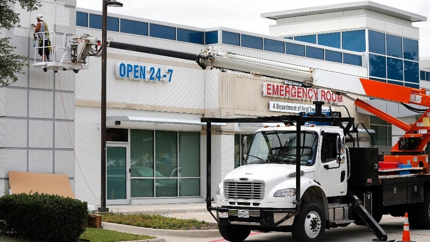 A worker makes repairs to an exterior wall of a First Choice Emergency Room, Thursday, Aug. 18, 2016, in Richardson, Texas. Freestanding emergency centers have sprouted in recent years across the suburban landscape, taking root in affluent neighborhoods and directly challenging nearby medical clinics and hospitals.  (AP Photo/Tony Gutierrez)